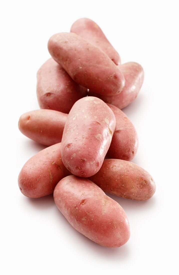 Red skinned 'Cherie' potatoes on a white surface