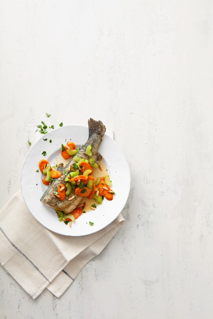 Baked trout with carrots, celery and pine nuts