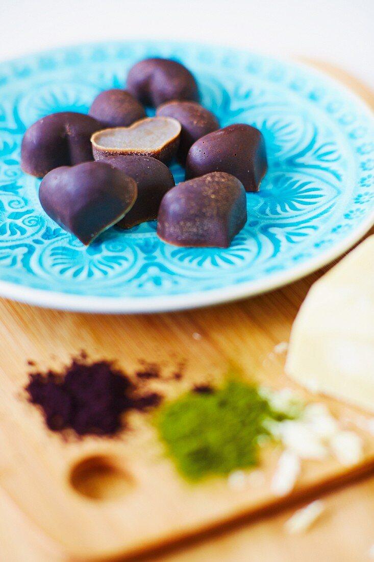 Detox truffle pralines made from cocoa butter, hemp seeds, acai and wheatgrass powder, stevia and carob powder