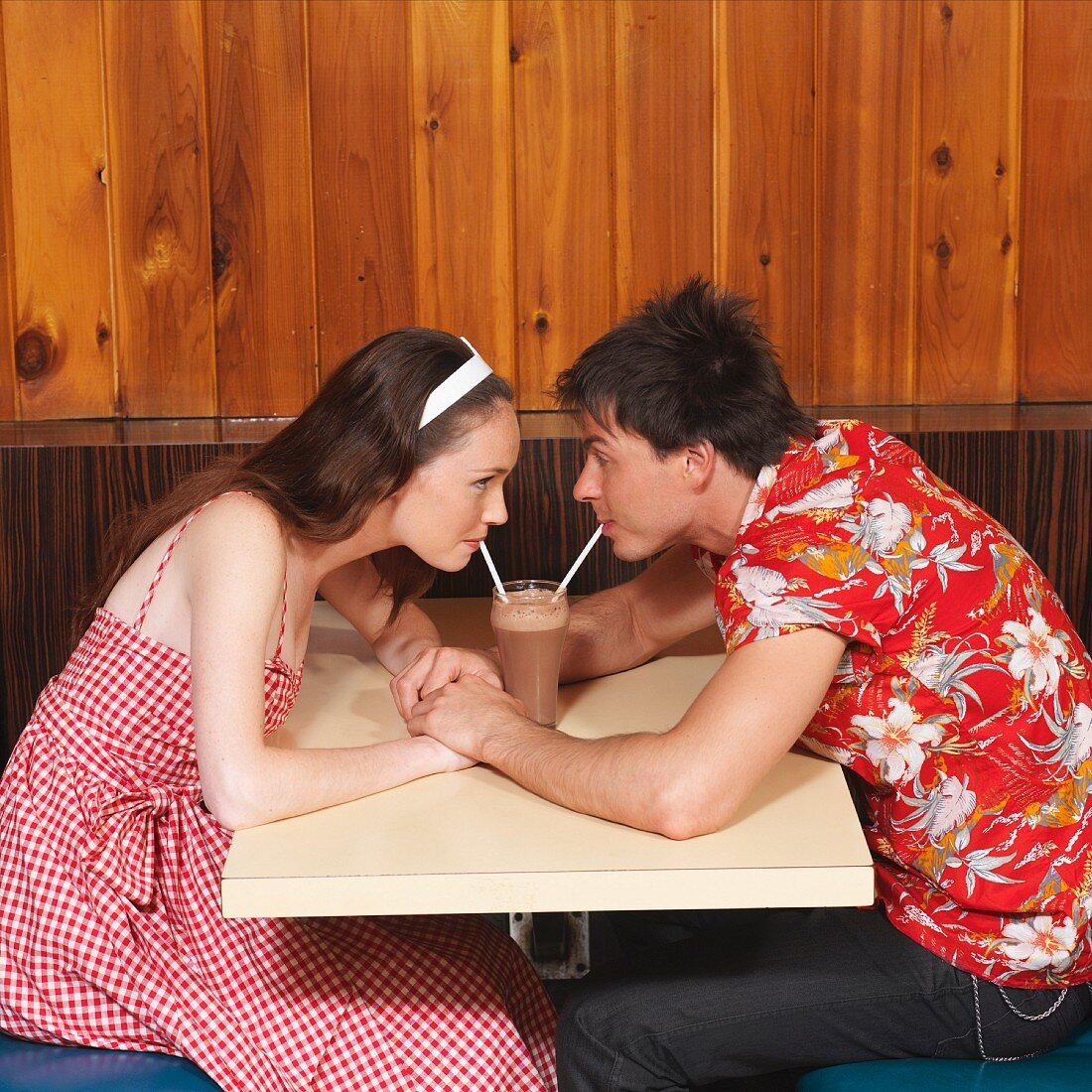 A couple drinking a milkshake in a diner