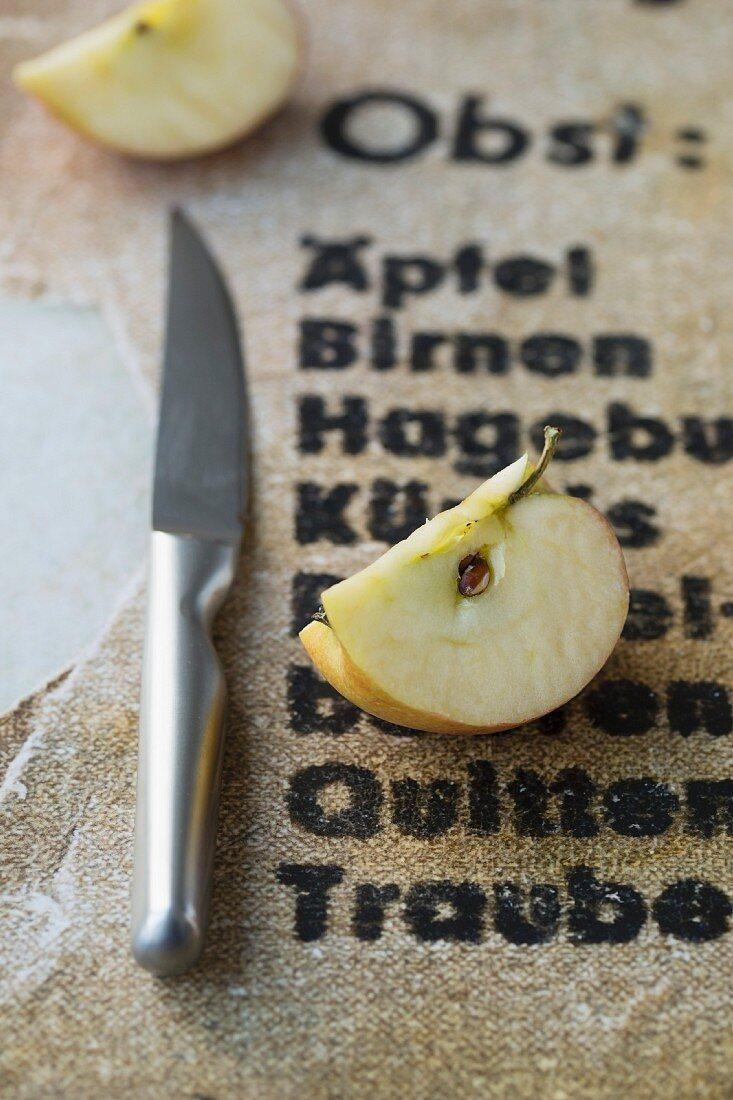 An apple quarter next to a knife