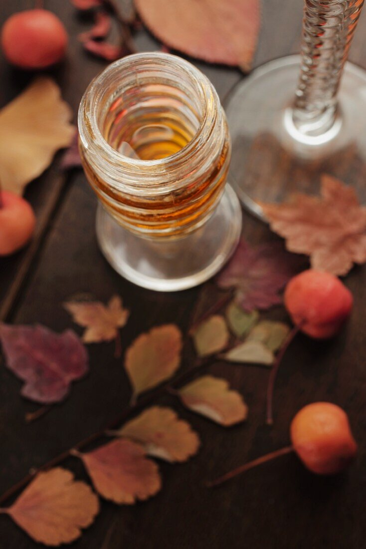 A glass of dessert wine with autumn leaves and berries on a wooden table