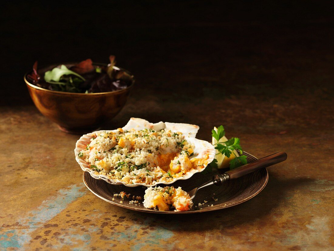 Gratinated prawns and langoustines in scallop shells garnished with lemon and coriander