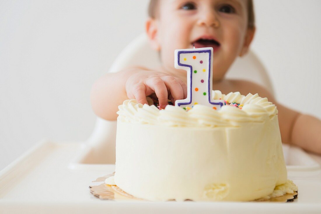 A happy baby reaching for his birthday cake
