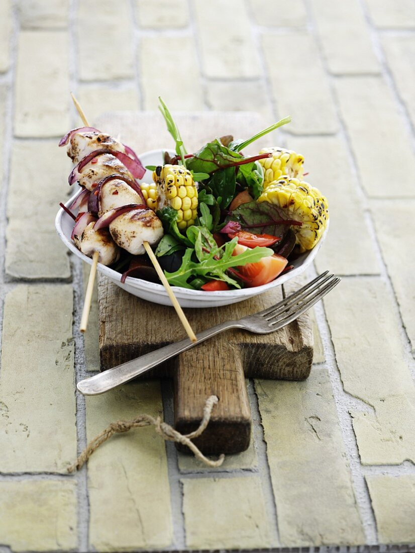 A chicken skewer with red onions, grilled corn on the cob and a salad