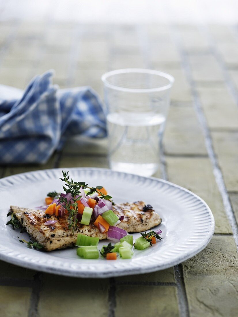 Grilled fish steak with a vegetable salad and thyme