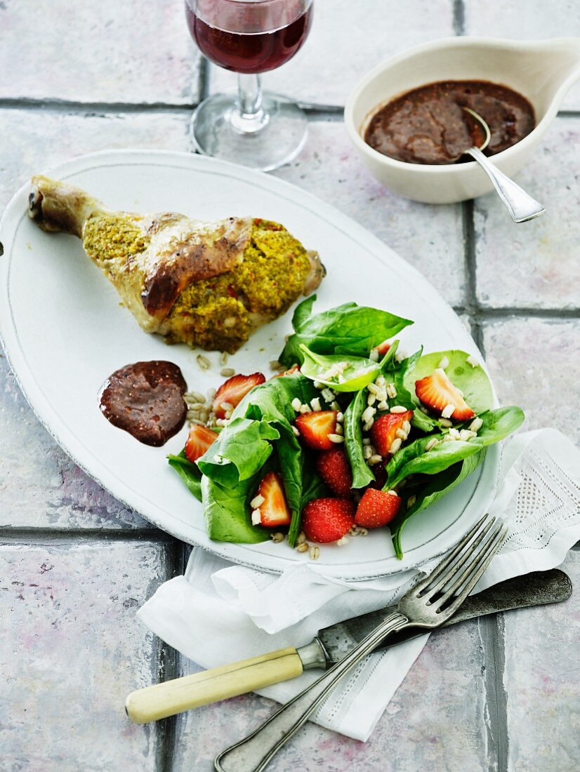 Chicken leg with a mustard crust served with strawberry salad