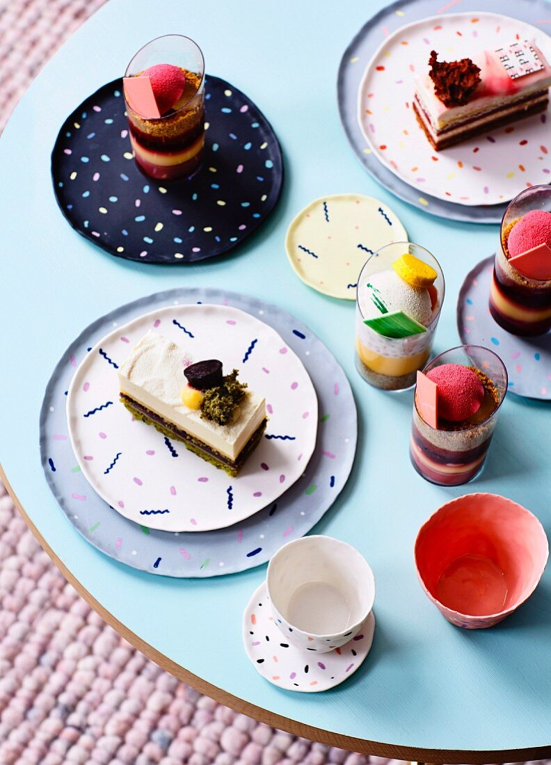 Desserts and cakes in glasses and on patterned plates on coffee table