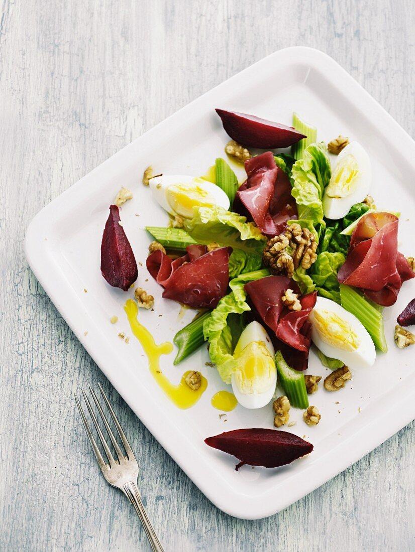 Salatteller mit Bresaola, Ei, Walnüssen, Sellerie und Roter Bete