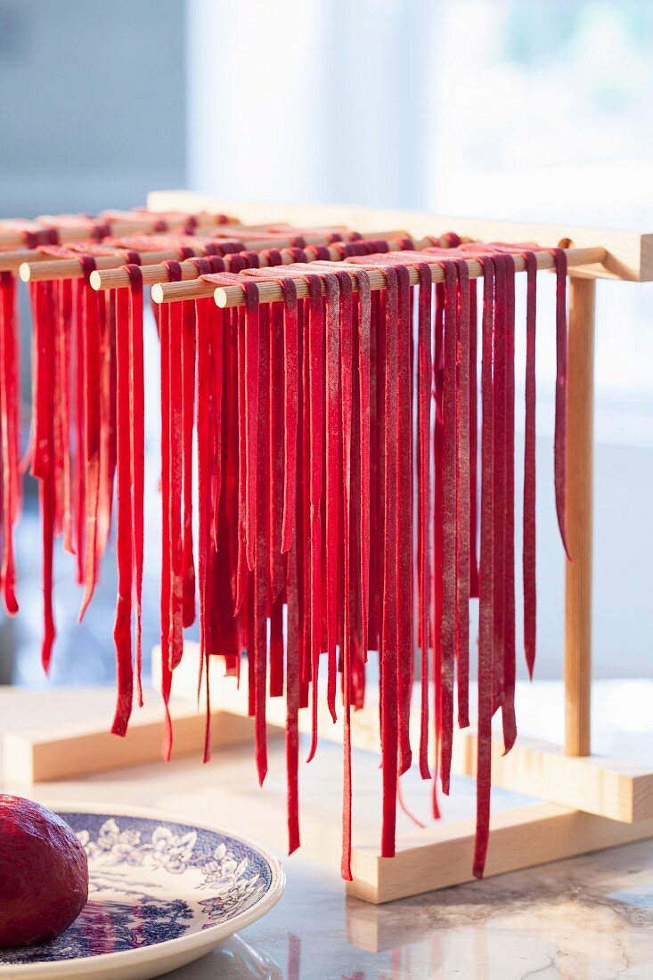 Homemade beetroot pasta drying on a wooden rack