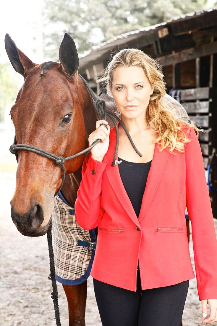 A young blonde woman wearing a red jacket next to a horse
