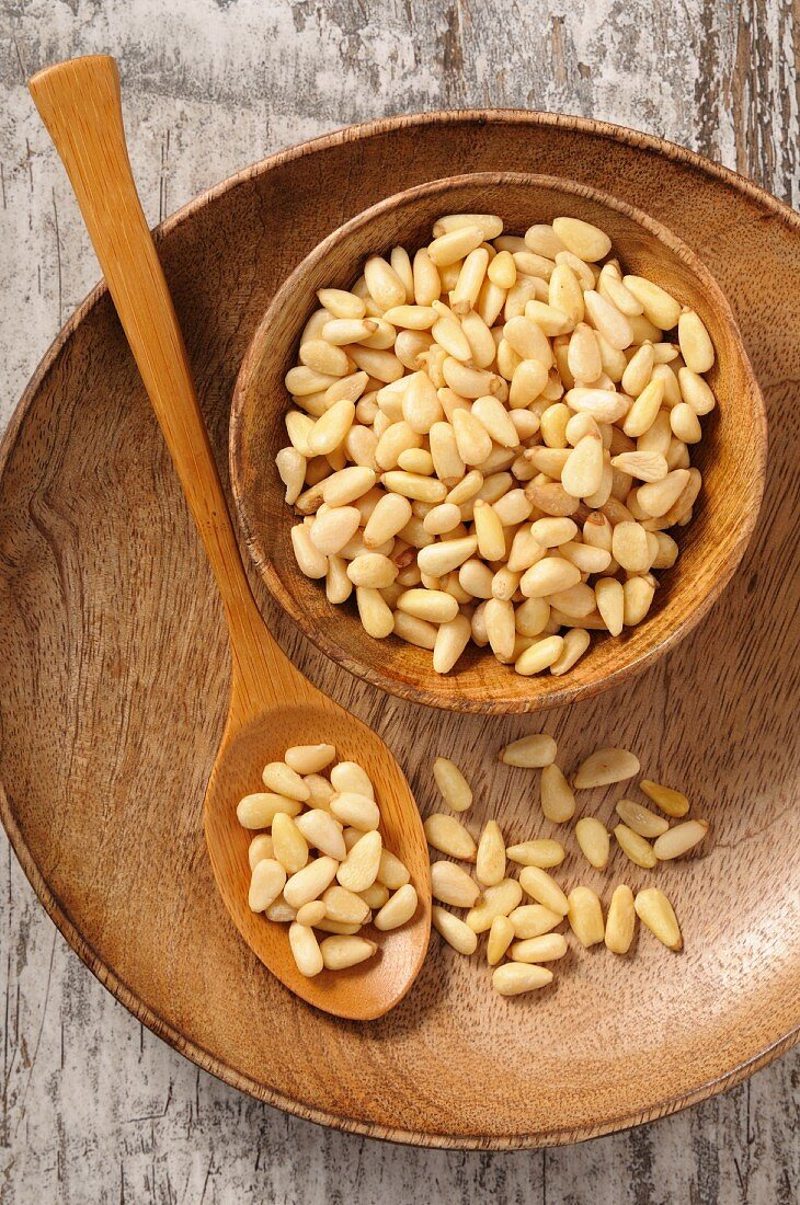 Pine nuts in a wooden bowl and on a spoon