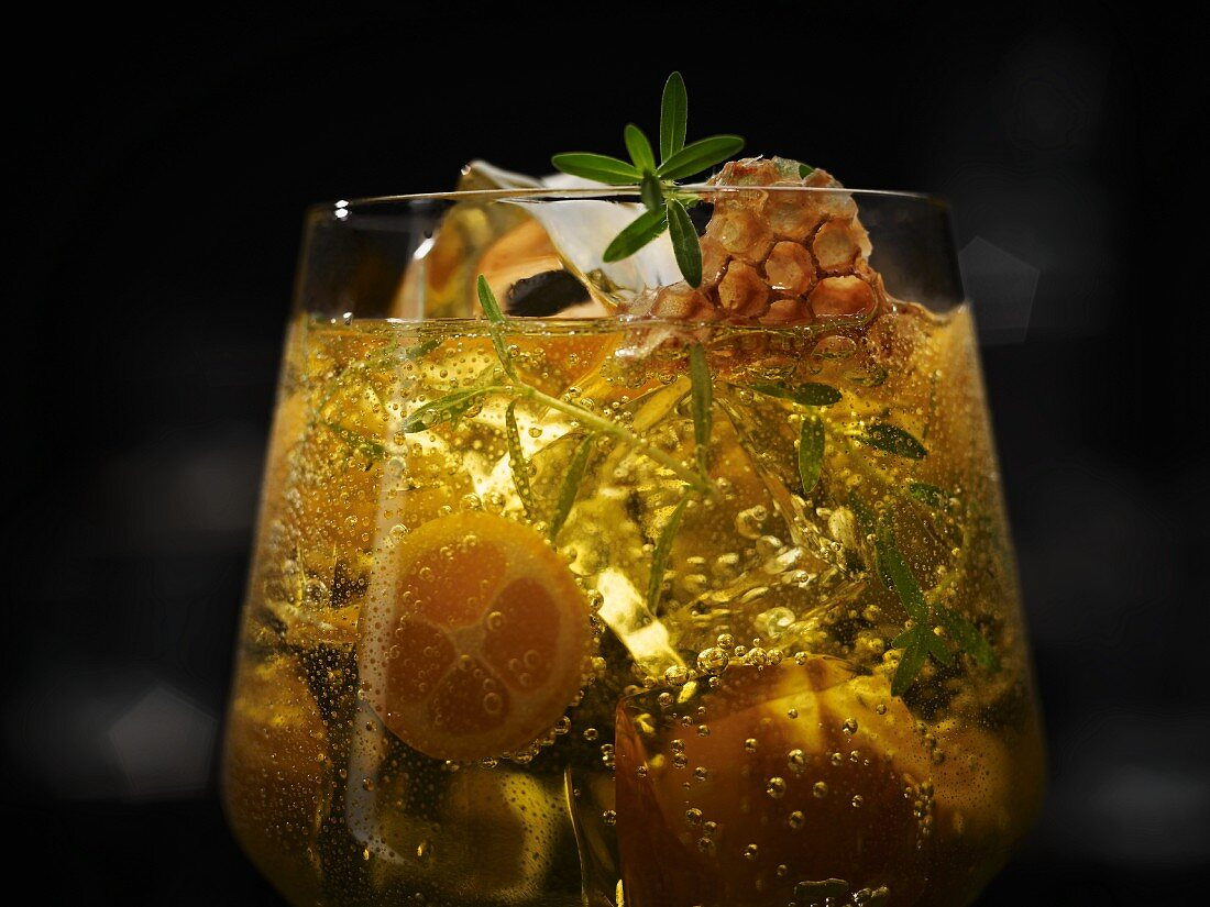 An exotic drink with honeycomb, kumquats, ice cubes and a herb garnish