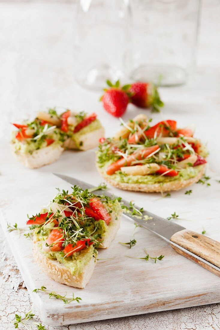 Bagel with avocado cream, strawberries and asparagus tips