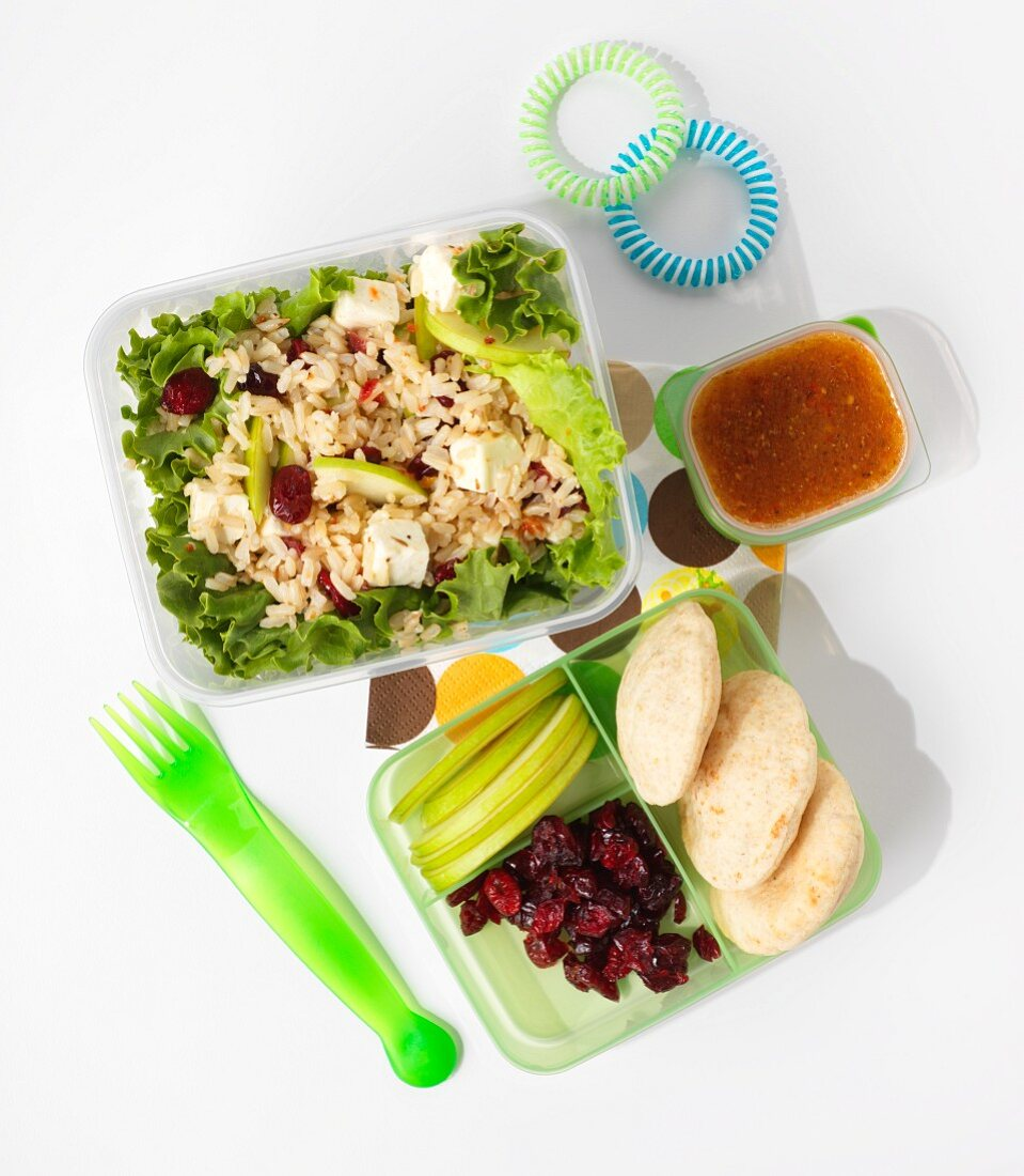 A healthy children's lunch: pilau with dried cranberries, apple and feta cheese