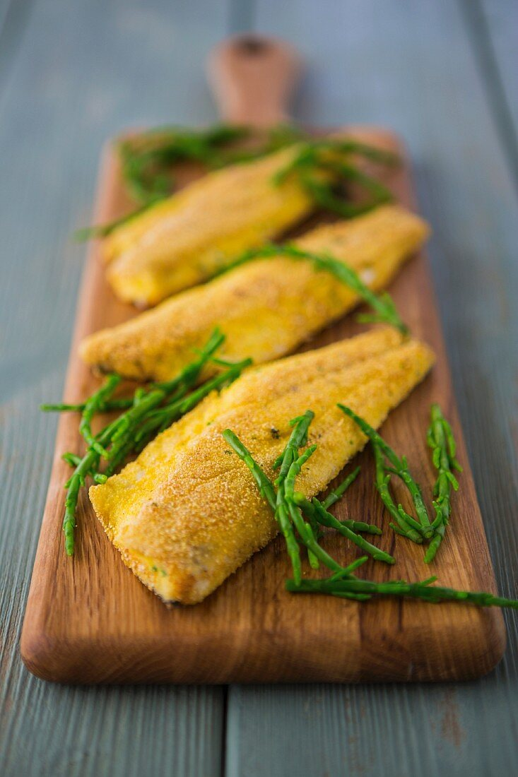 Breaded seabass fillets with a polenta and herb coating, served with samphire on a wooden board