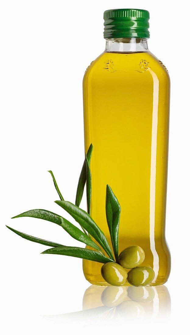 A bottle of olive oil, a sprig of olive leaves and green olives