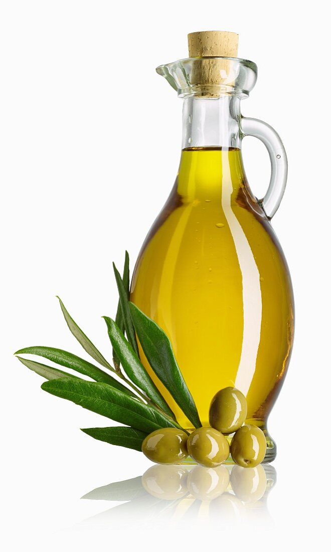 A carafe of olive oil, a sprig of olive leaves and green olives