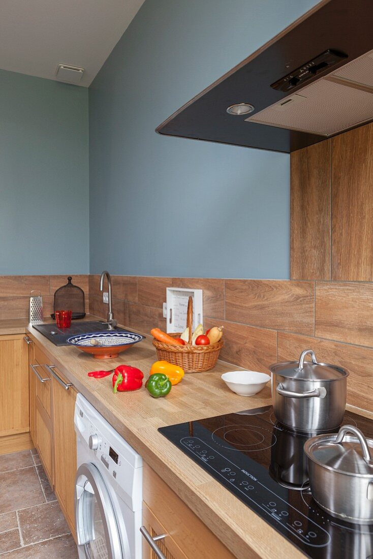 Kitchen counter with pale wooden worksurface and cupboards against wall painted pale blue