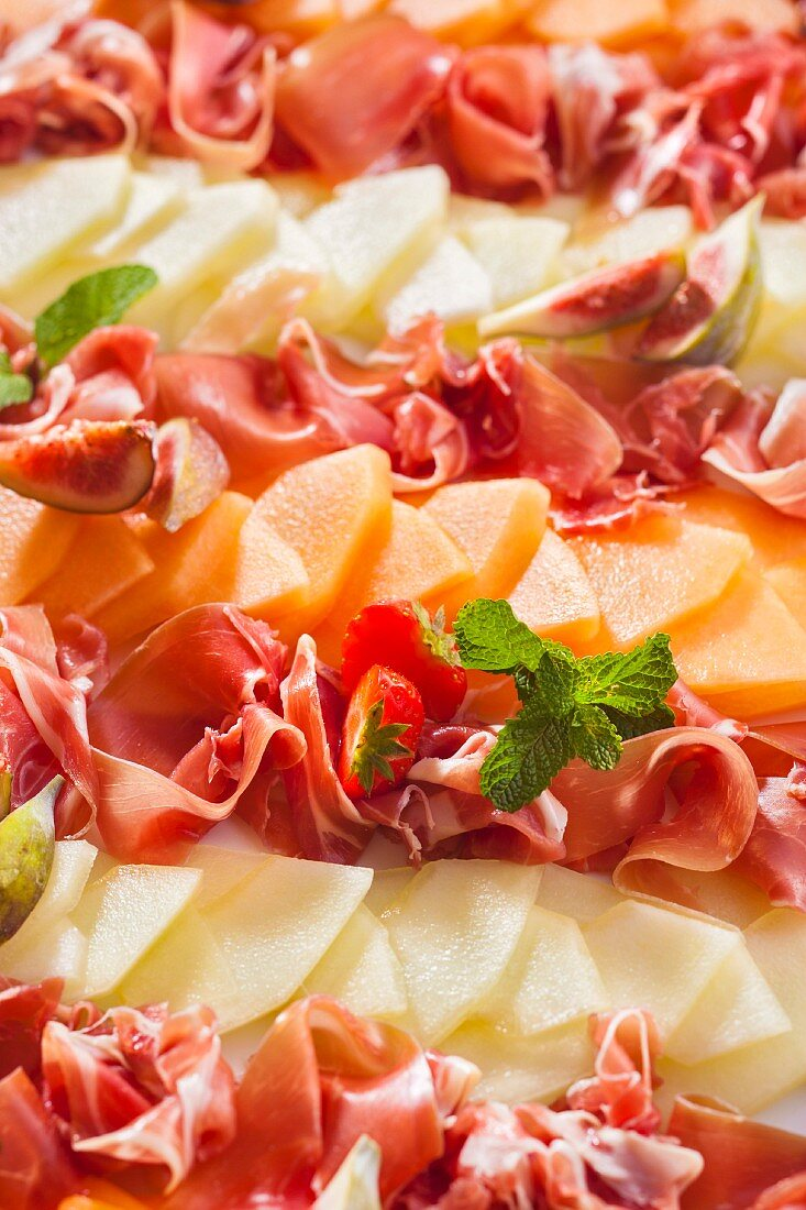 A party platter of melon, ham and figs
