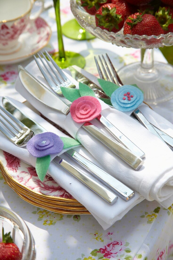 Hand-crafted napkin rings made from romantic, pastel felt flowers on festive garden table