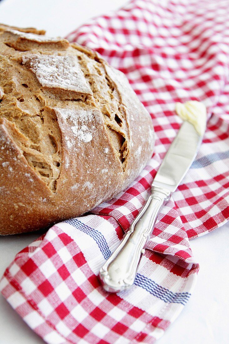 Crusty bread and a knife with butter on a checked cloth