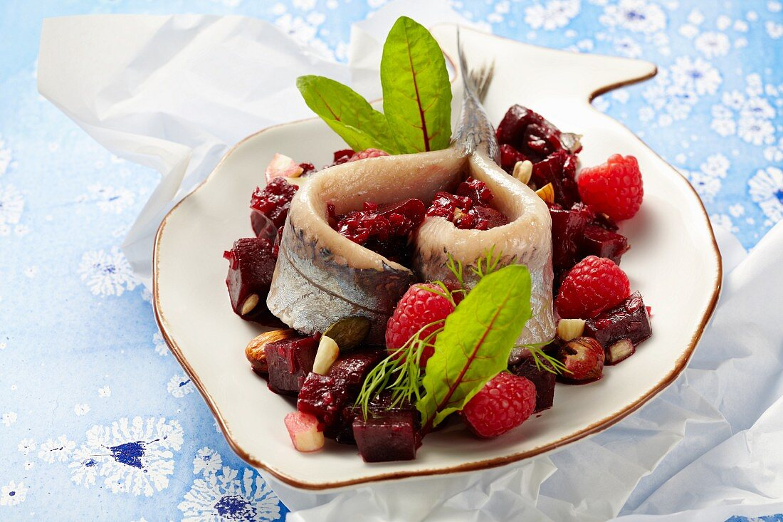 Soused herring on a beetroot salad with raspberries and nuts