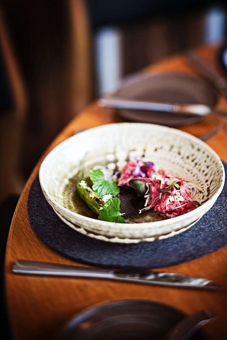 Raw wagyu beef shoulder with enoki mushroms, wasabi leaves and chillis