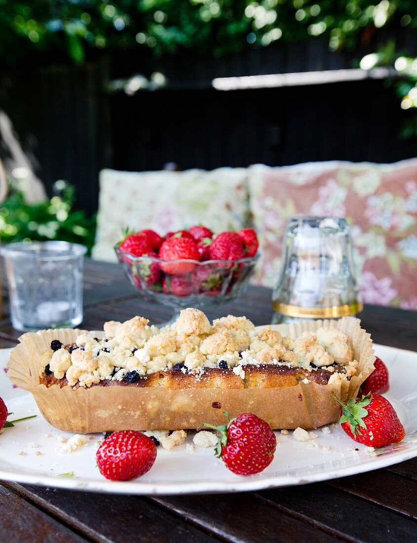 Home-made berry cake with crumble topping and fresh strawberries on cake plate on table outdoors