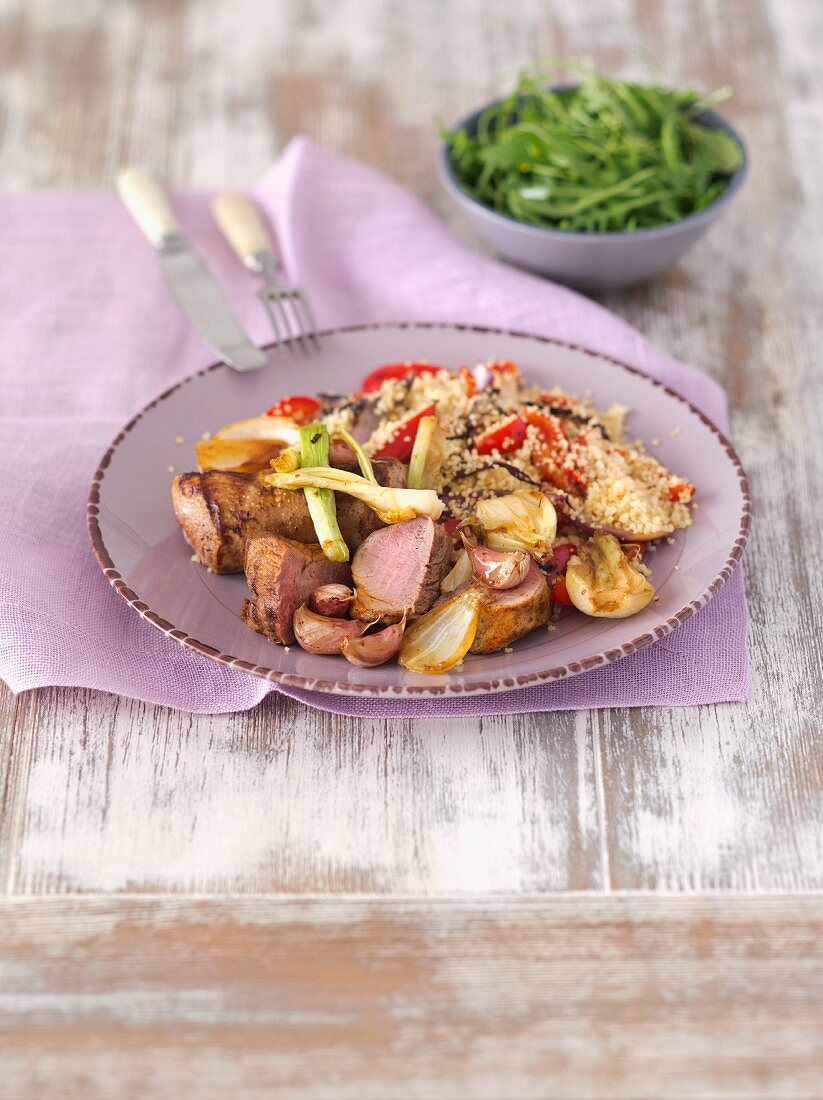 Oven-roasted pork loin with onions and garlic on a bed of couscous with grilled vegetables