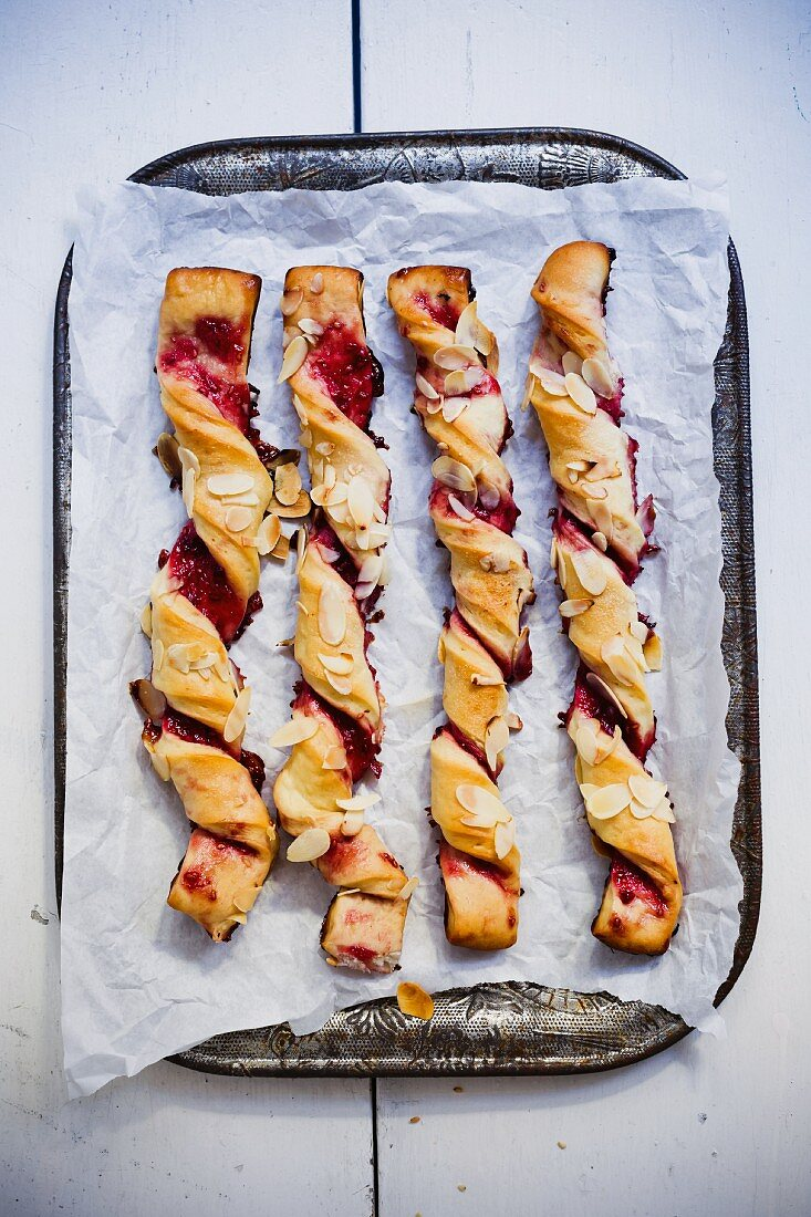 Sweet puff pastry sticks with jam on a tray (seen from above)