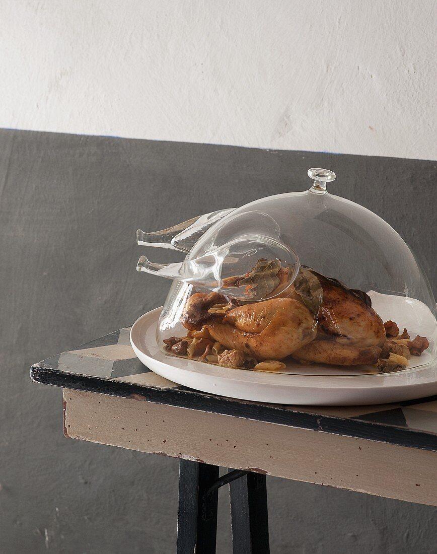 Roast chicken with mushrooms under a glass chicken-shaped cloche