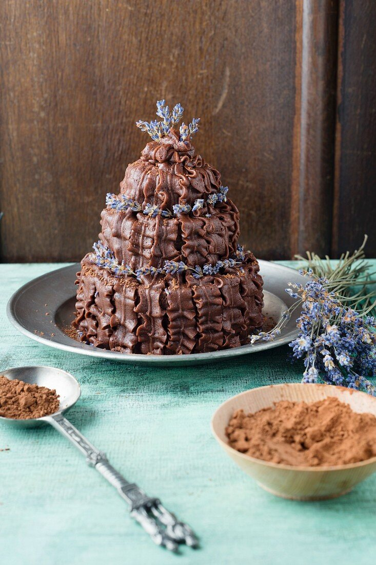 A chocolate cake decorated with chocolate butter cream ruffles and lavender flowers