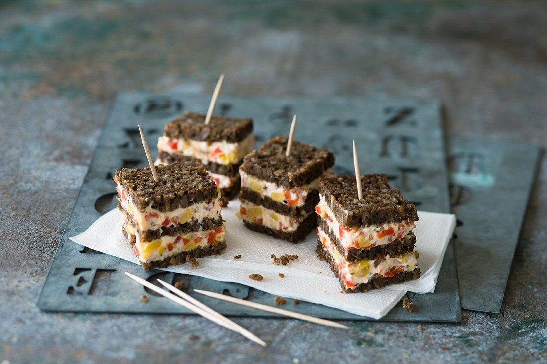 Black bread cubes with sweetcorn and pepper cream cheese