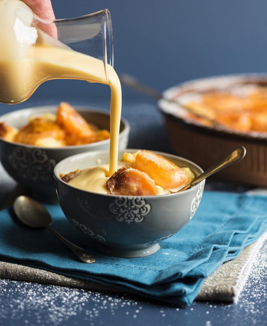 Vanilla sauce being poured over apricot clafoutis