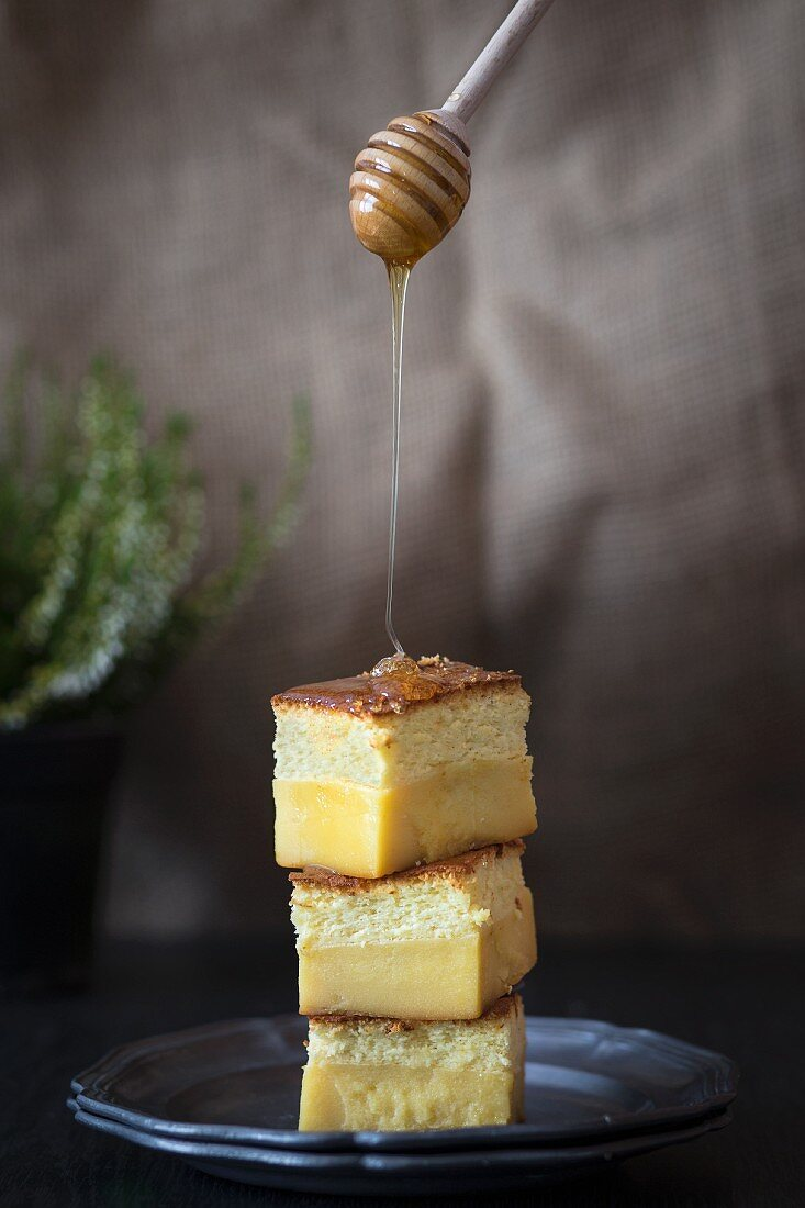 Honey being drizzled on to pudding cake
