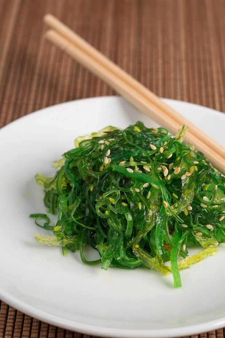 Wakame salad with sesame seeds on a wooden mat