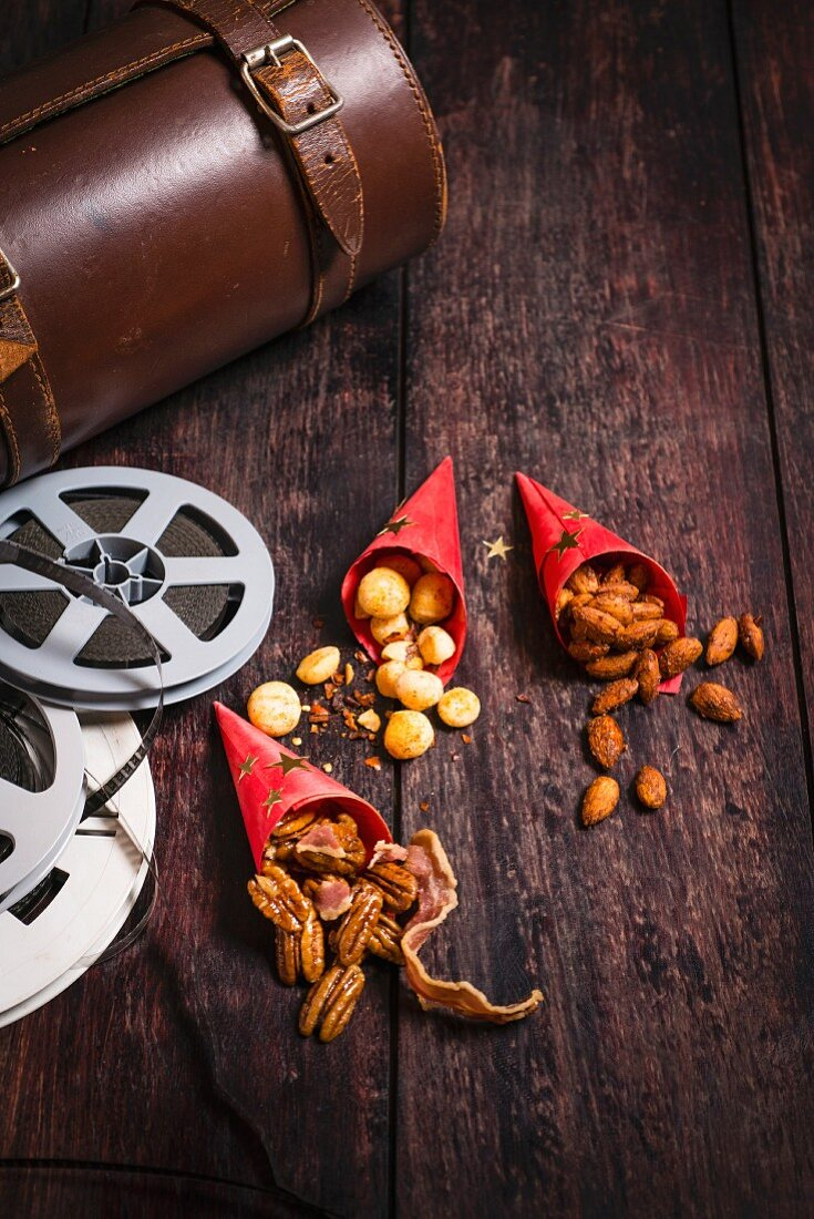 Three types of nuts in paper bags next to film-themed decorations