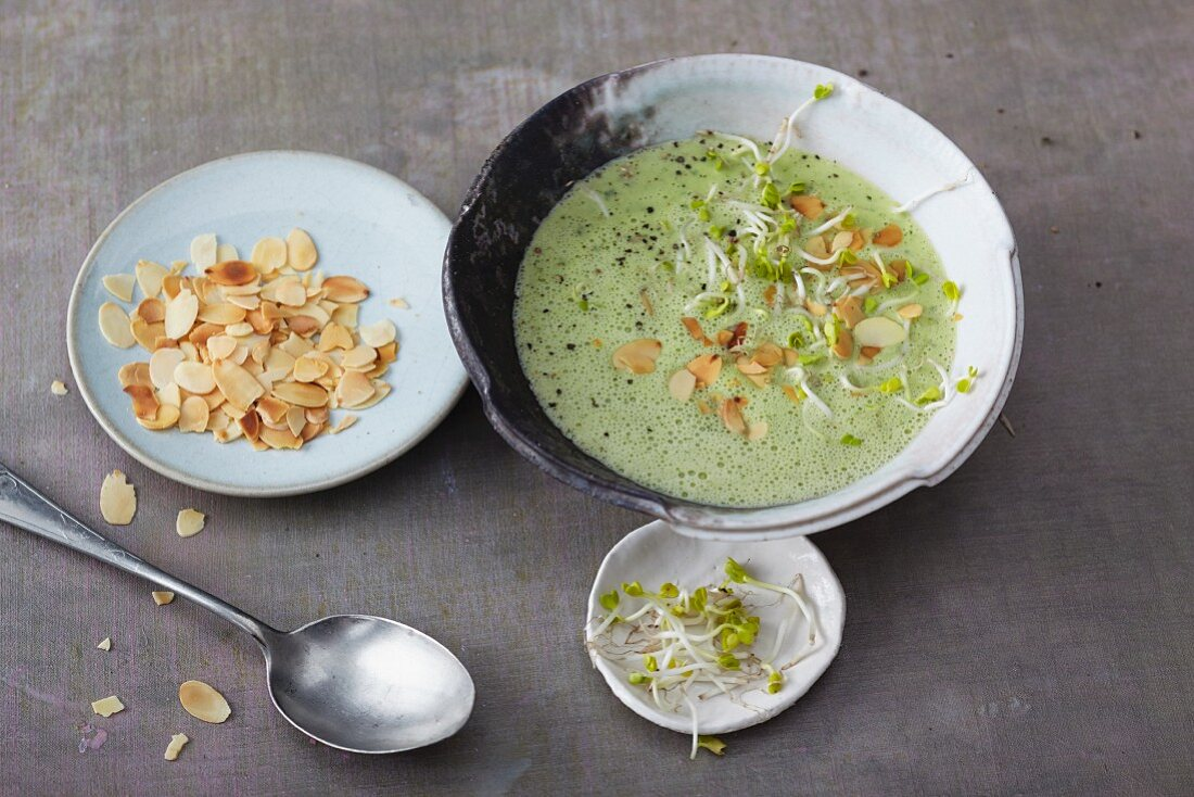 Vegetarian herb soup with white asparagus and flaked almonds