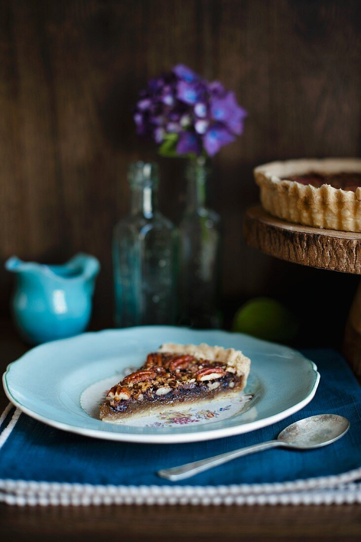A slice of pecan tart on a light blue plate in front of a jug of cream, flowers and a cake stand