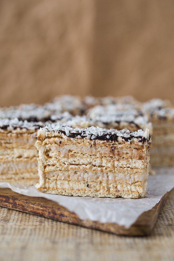 A layered sponge cake with walnut and coconut cream glazed with ganache