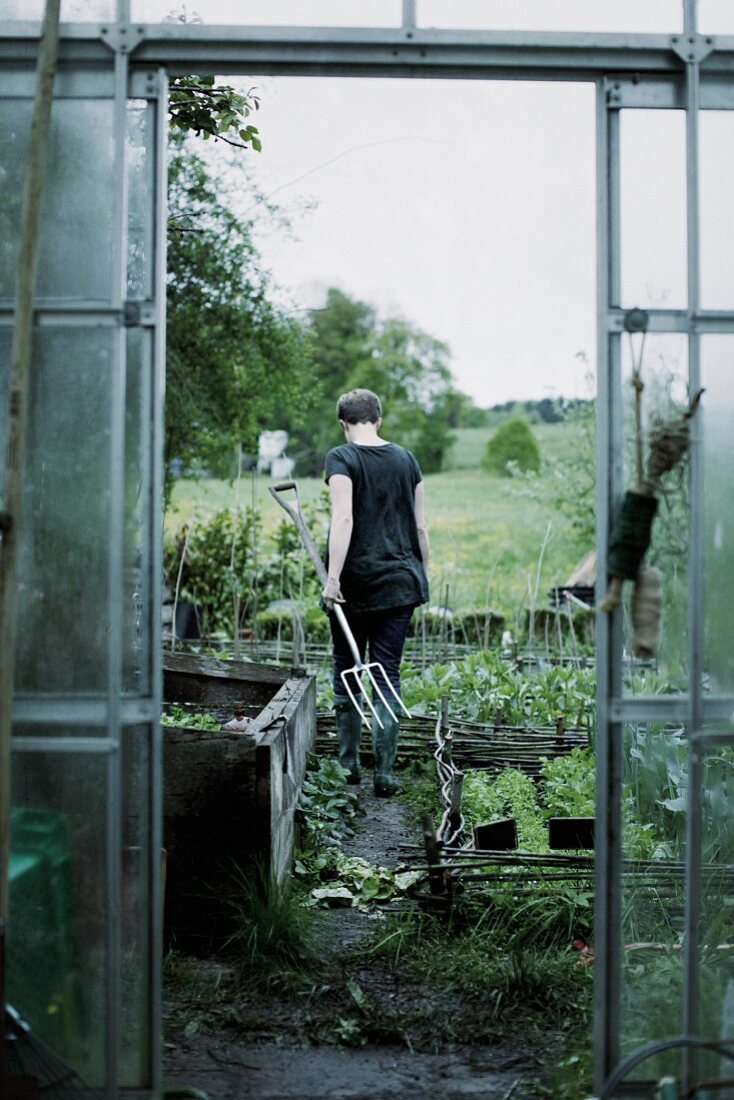 Woman carrying garden fork in vegetable patch