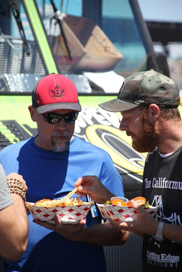 Two men eating fries at a food truck festival in California, USA
