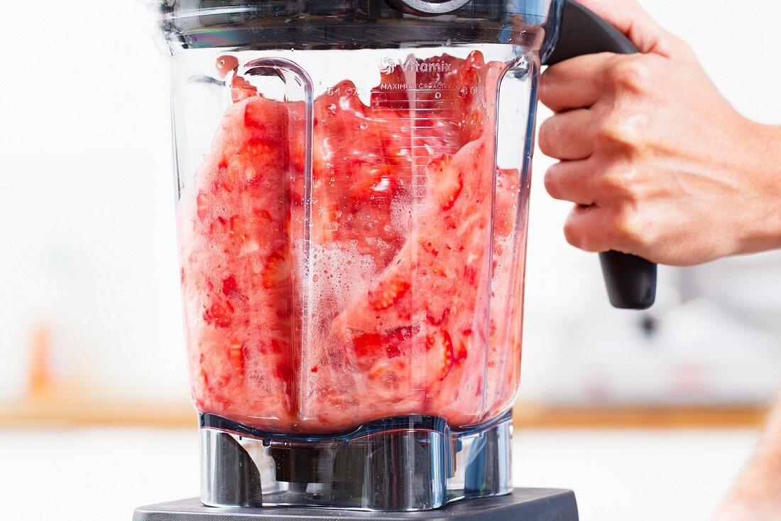 Strawberries being puréed in a blender