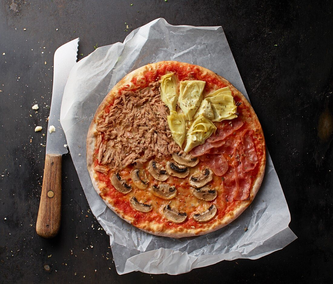 A tuna, mushroom, Parma ham and artichoke pizza on a piece of paper with a knife