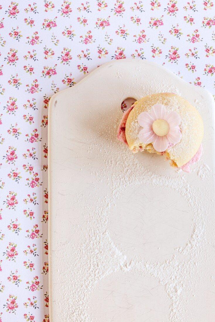 A whoopie pie with raspberry cream, bitten