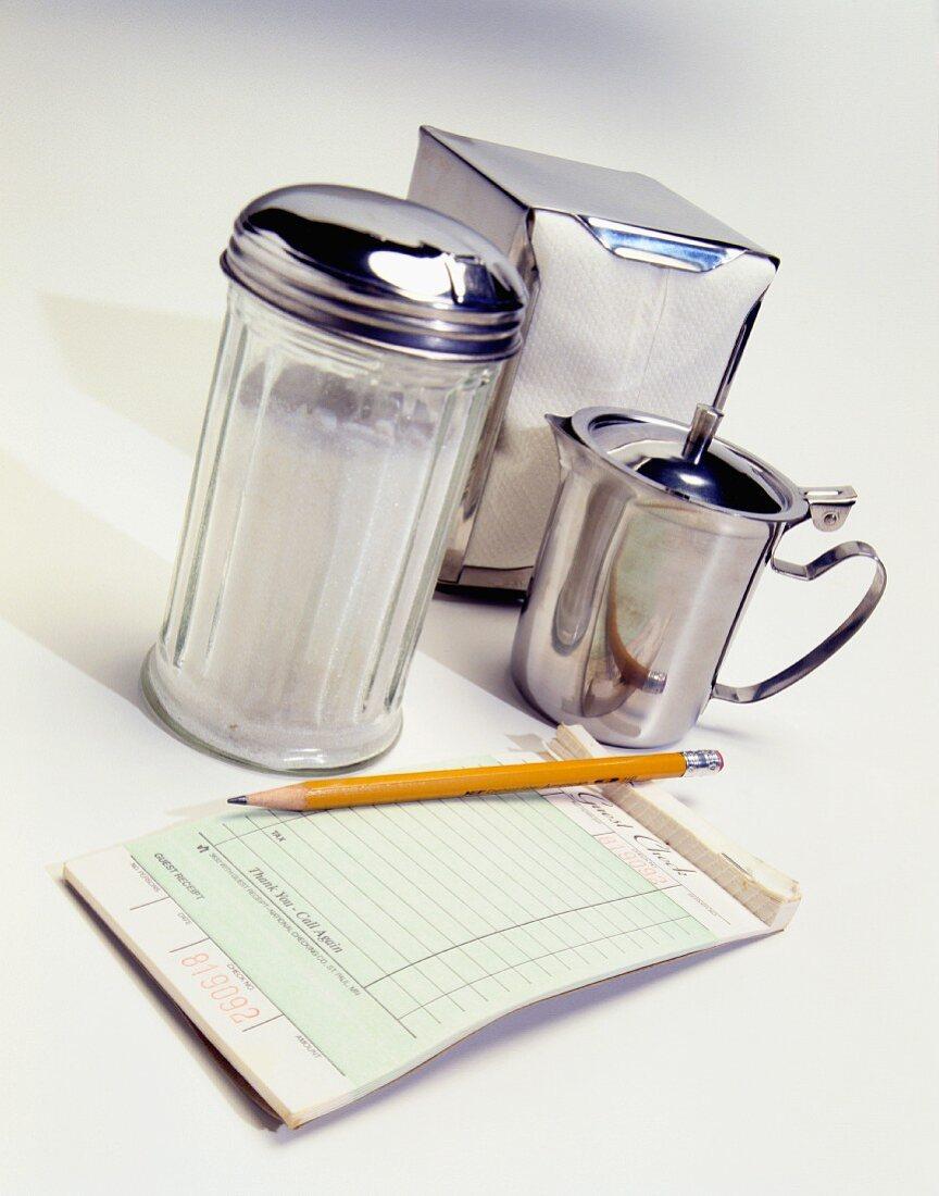 An order pad, a pencil, a sugar shaker, a jug of cream and a napkin dispenser