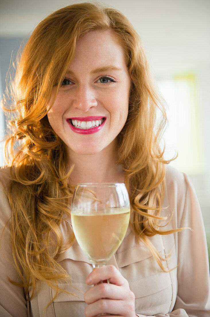 An attractive woman holding a glass of wine