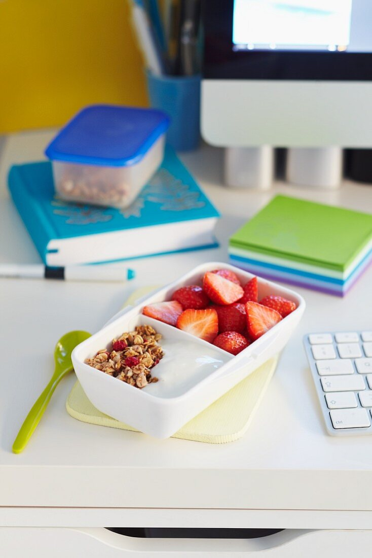 Yoghurt muesli and strawberries in a Tupperware box on a desk
