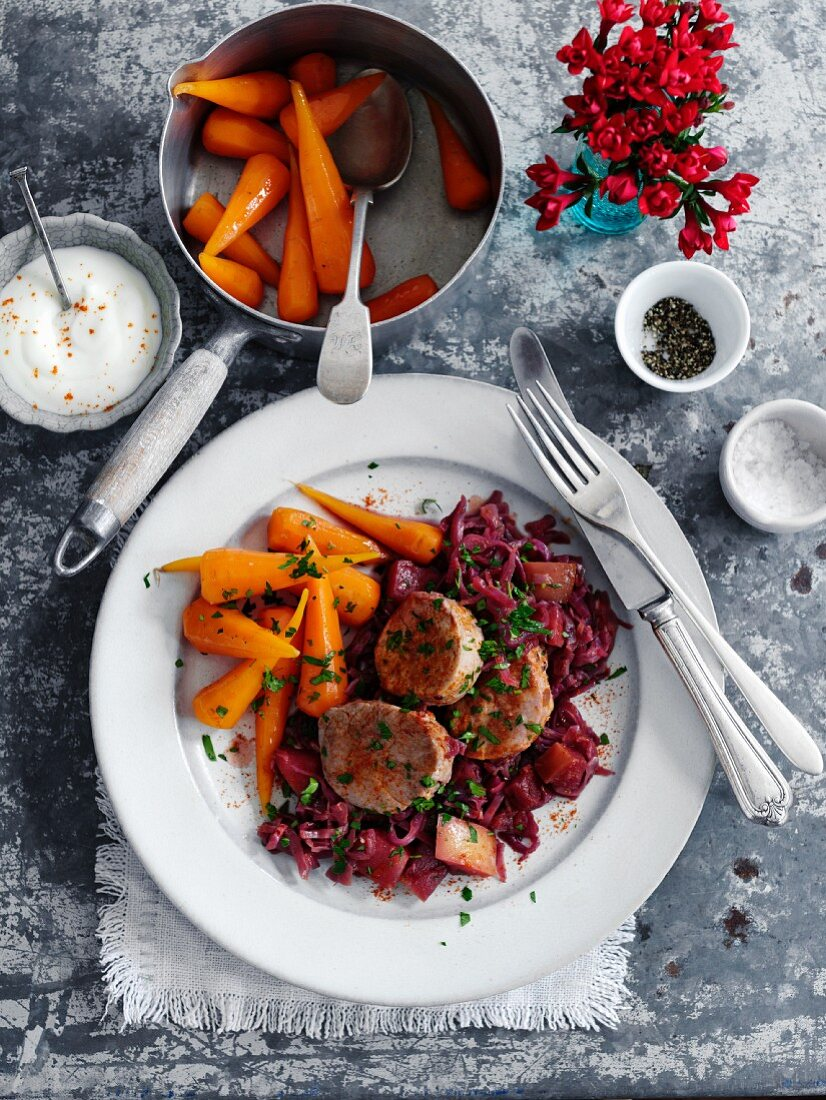 Braised pork on a bed of red cabbage with carrots (seen from above)